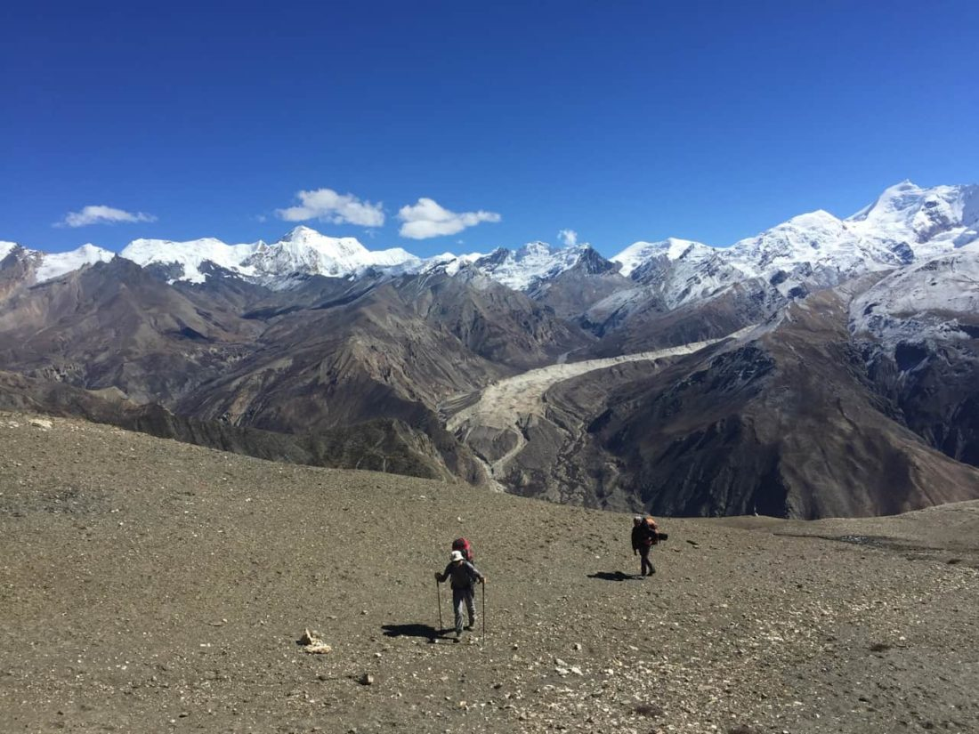 himalaya reise, zwei kunden im aufstieg zum pass, mit bergpanorama im hintergrund