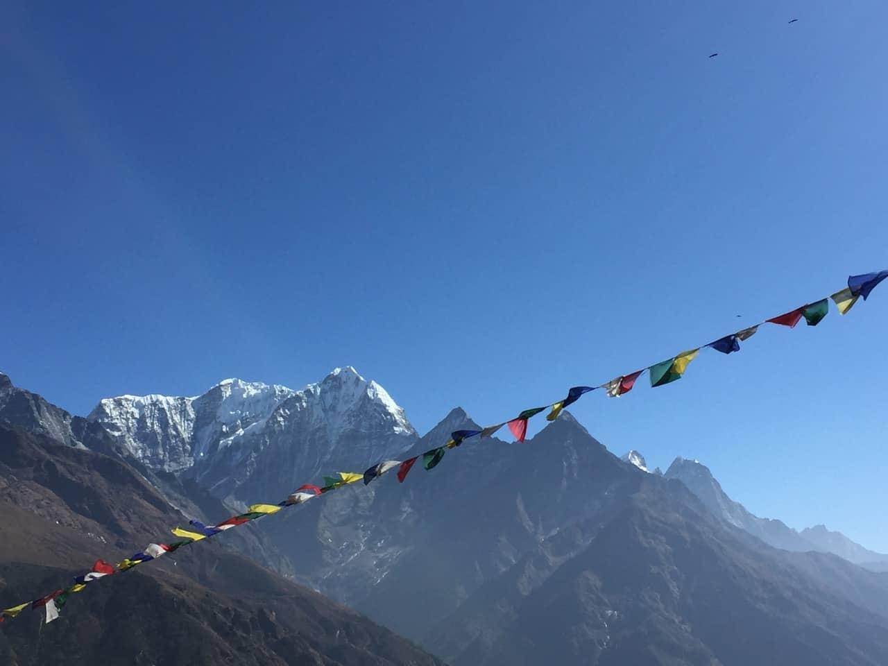 gebetsfahnen vor himalaya bergen und tiefblauem himmel