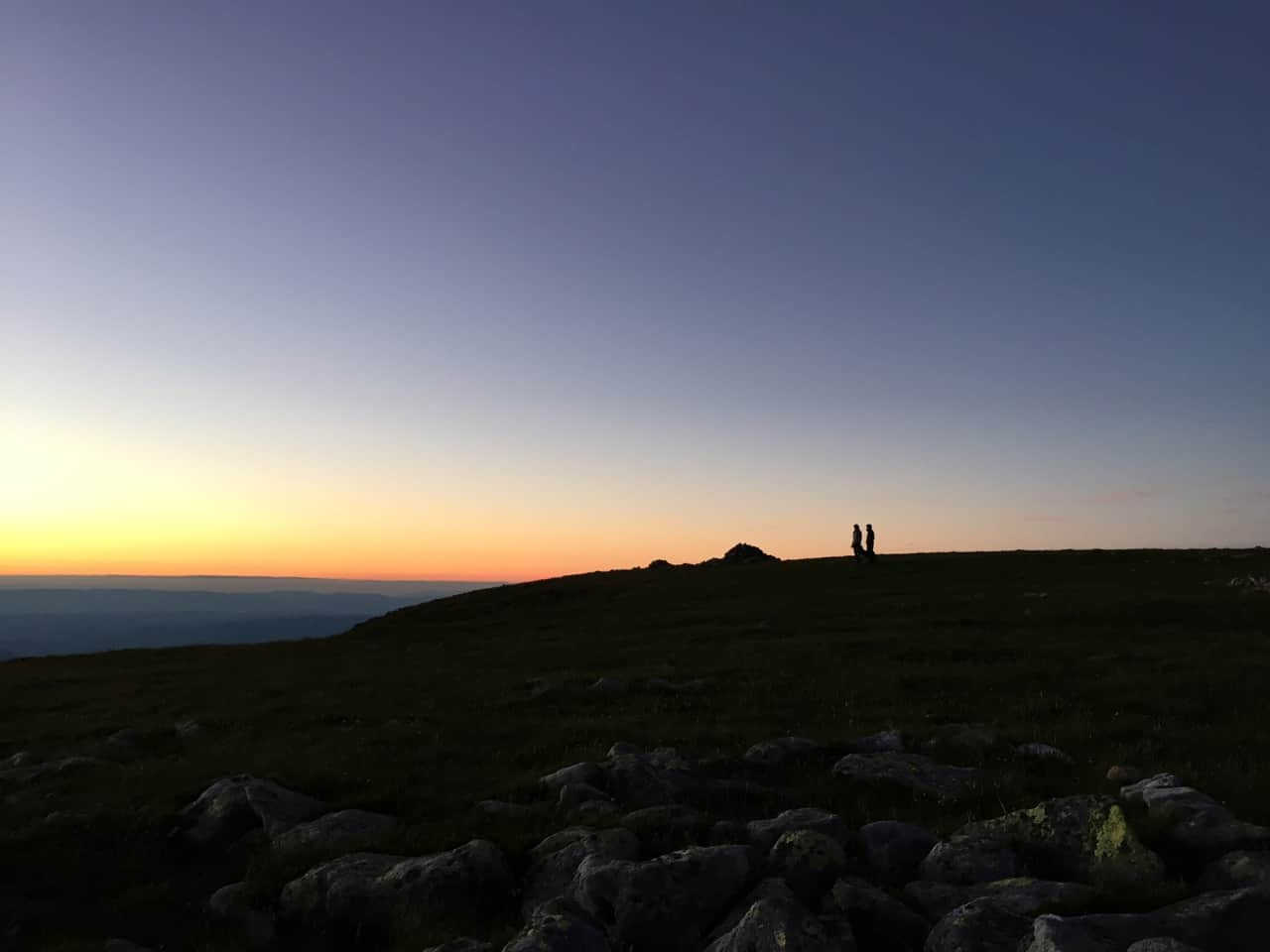 auszeit schweiz, zwei menschen geniessen den sonnenuntergang auf dem berg