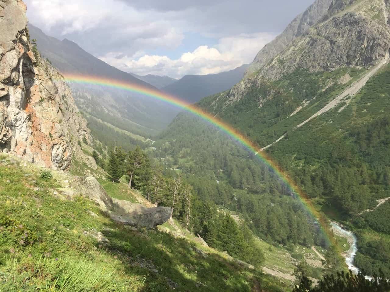 auszeit schweiz mit regenbogen über grünem tal