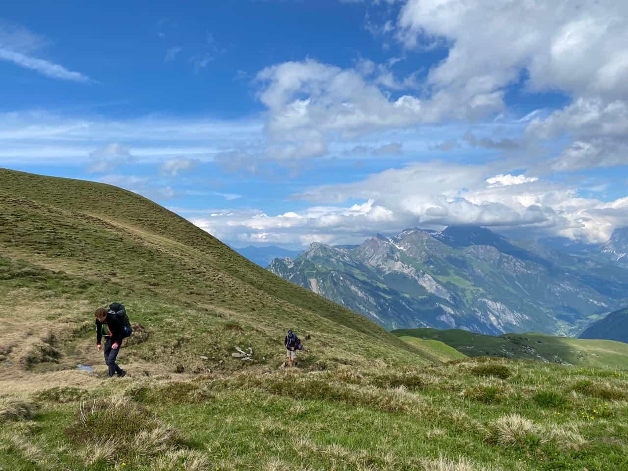 auszeit schweiz, zwei wanderer steigen den berghang hoch