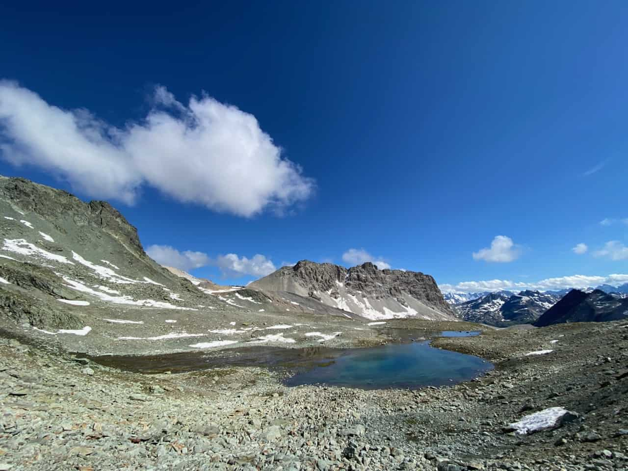 auszeit schweiz im graubünden, türkis farbener bergsee in karger gerölllandschaft
